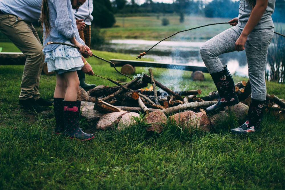 Familie steht am Lagerfeuer im Rauch und röstet Marshmallows