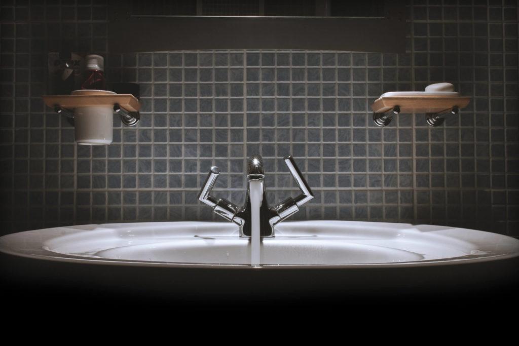 Badezimmer Waschbecken mit laufendem Wasserhahn