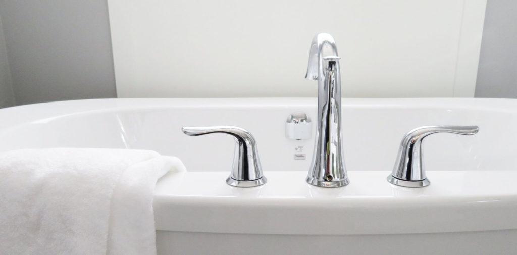 Weisse Badewanne mit übergeworfenem Handtuch